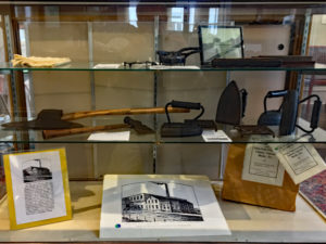 Sad irons and axes in a display case
