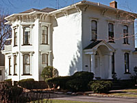 Color photo of an ornate white house.